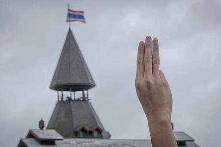Ein pro-demokratischer Demonstrant erhebt während einer Demonstration im Sanam-Luang-Park drei Finger als Symbol des Widerstands. Foto: Wason Wanichakorn/AP/dpa