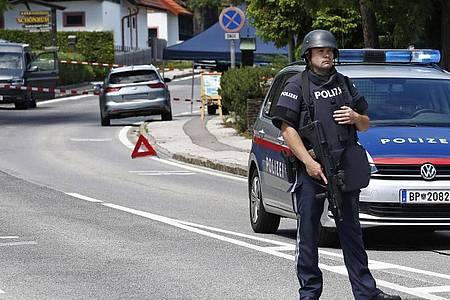 Ein bewaffneter Polizist sichert einen Straßenabschnitt am Tatort einer Tötung in der Gemeinde Villach. Foto: Gert Eggenberger/APA/dpa