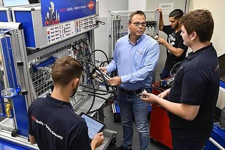 Thorsten Herkert, Technischer Ausbildungsleiter bei Knipex, erklärt den Industriemechaniker-Azubis Noah Hecker und Luca Tremper (v.l.n.r.) die Steuerung der Hydraulikanlage. Foto: Kirsten Neumann/dpa-tmn