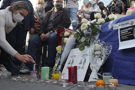 Eine Frau zündet eine Kerze an: Zahlreiche Menschen haben sich nach der brutalen Ermordung eines Lehrers am Wochenende zu einer Solidaritätsdemonstration in Paris versammelt. Foto: Michel Euler/AP/dpa