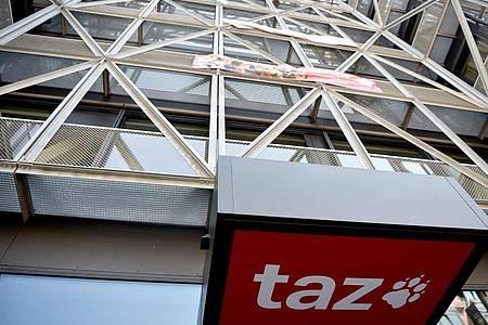 """Das Logo der Tageszeitung """"taz"""" ist am Eingang des Redaktionsgebäudes in Berlin-Mitte zu sehen. Foto: Sven Braun/dpa"""