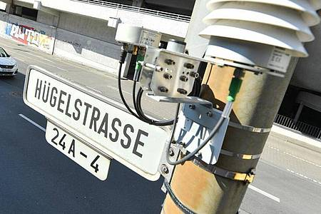 Autos fahren auf der Darmstädter Hügelstraße an einer Luftmessstation vorbei. Foto: Arne Dedert/dpa