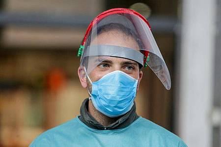 Ein Mitarbeiter des provisorischen Krankenhauses auf der Madrider Messe trägt Mund- und Gesichtsschutz. Foto: Ricardo Rubio/Europa Press/dpa