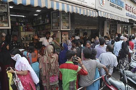 Inderinnen und Inder stehen während der Corona-Pandemie dicht gedrängt vor einem Lebensmittelgeschäft an. Foto: Rafiq Maqbool/AP/dpa