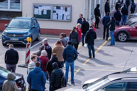 Hier ist Geduld gefragt: Apotheker und Mitarbeiter von Versorgungsbetrieben stehen auf dem Gelände des Zuckerwerks in Anklam in einer langen Schlange am Verkaufsbüro an. Foto: Jens Büttner/dpa-Zentralbild/dpa