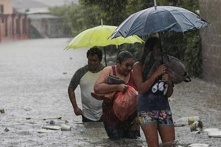 Menschen bringen sich inSicherheit. Aufgrund des Tropensturms «Eta» wurden in Honduras Überschwemmungen und Erdrutsche gemeldet. Etwa 30 Ortschaften wurden von der Außenwelt abgeschnitten, weil Brücken einstürzten. Foto: Delmer Martinez/AP/dpa