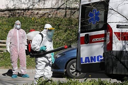 Ein Mann, der Schutzkleidung trägt, desinfiziert in Belgrad einen Krankenwagen. Serbien will die Ausbreitung des Coronavirus mit rigorosen Maßnahmen unterdrücken. Wer das Sars-CoV-2-Virus trägt, aber keine oder nur leichte Symptome hat, soll künftig strikt isoliert werden. Foto: Darko Vojinovic/AP/dpa