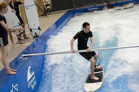 Redakteur Tobias Hanraths beim Surfversuch im Berliner Wellenwerk - hier noch mit anfängerfreundlicher Haltestange. Foto: Florian Schuh/dpa-tmn