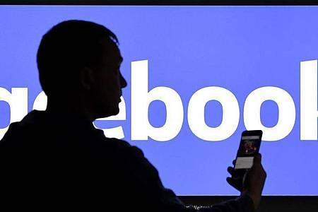 Ein Mann mit Smartphone steht vor einem Monitor mit dem Logo von Facebook. Foto: Carsten Rehder/dpa