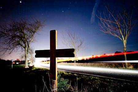 Ein Kreuz zur Erinnerung an einen Verkehrstoten an einer Landstraße. Foto: picture alliance / Julian Stratenschulte/dpa