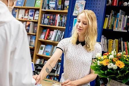 Klingelnde Kassen:Sophie Schmale macht eine Ausbildung zur Buchhändlerin in der Tegeler Bücherstube in Berlin. Foto: Zacharie Scheurer/dpa-tmn