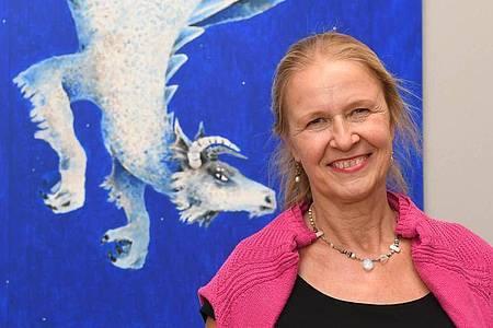 Cornelia Funke vor ihrem Werk «Saum des Himmels» aus dem Jahr 2016. Foto: Uli Deck/dpa