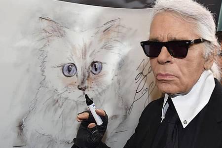 Der Modedesigner Karl Lagerfeld steht 2015 bei der Vernissage «Corsa Karl und Choupette» für seinen Fotokalender im Palazzo Italia an einer Zeichnung seiner Katze. Foto: Jens Kalaene/dpa-Zentralbild/dpa