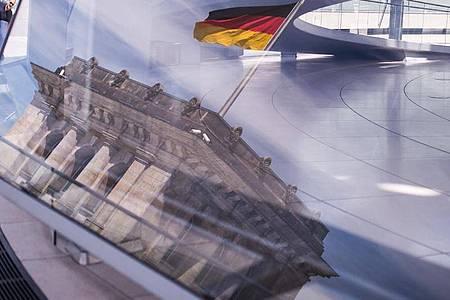 Eine Deutschland-Fahne spiegelt sich in der Kuppel des Reichstagsgebäudes. Foto: Sophia Kembowski/dpa