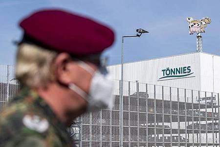 Ein Soldat auf der Bundeswehr steht vor dem Gebäude der Fleischfabrik Tönnies in Rheda-Wiedenbrück. Die Bundeswehr unterstützt bei Tests der Mitarbeiter auf das Coronavirus. Foto: David Inderlied/dpa
