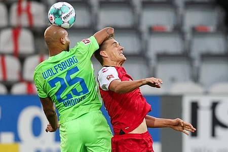 Wolfsburgs John Anthony Brooks (l) kommt vor Freiburgs Nils Petersen an den Ball. Foto: Tom Weller/dpa