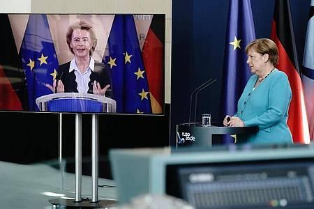 Bundeskanzlerin Angela Merkel (CDU) hört im Foyer des Bundeskanzleramtes EU-Kommissionspräsidentin Ursula von der Leyen (CDU), die per Video zugeschaltet ist, zu. Foto: Kay Nietfeld/dpa