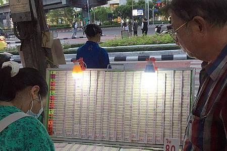 Vor einem Tempel werden Lotterielose verkauft. Foto: Dow Kaewjinda/dpa