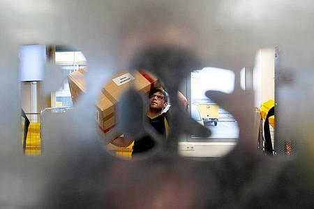 Alexander Seiffert, Fachkraft für Kurier-, Express- und Postdienstleistungen, trägt ein Paket zu einem Förderwagen. Foto: Klaus-Dietmar Gabbert/dpa-tmn