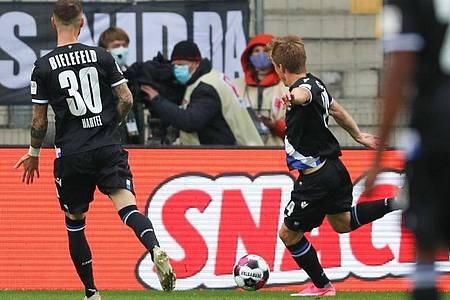 Der Bielefelder Joan Simun Edmundsson schießt den Ball zum 1:0 ins Netz. Die Arminia feiert den ersten Bundesliga-Sieg seit über elf Jahren. Foto: Friso Gentsch/dpa