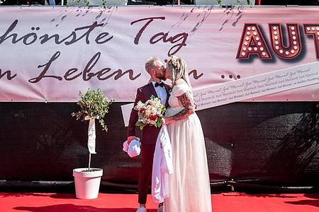 Das Brautpaar Janine und Philip Scholz (l) bei ihrer Trauung im Autokino. Foto: Fabian Strauch/dpa
