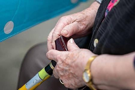 Eine Seniorin sitzt mit ihrem Gehstock im Garten im Pflegeheim. Foto: Daniel Karmann/dpa