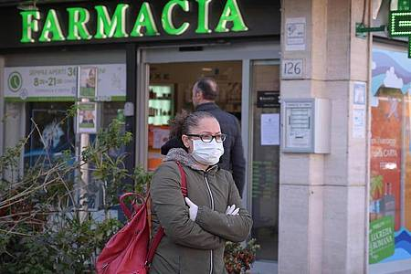 Eine Frau mit Mundschutz steht vor einer Apotheke in Rom. Foto: Alfredo Falcone/LaPresse via ZUMA Press/dpa