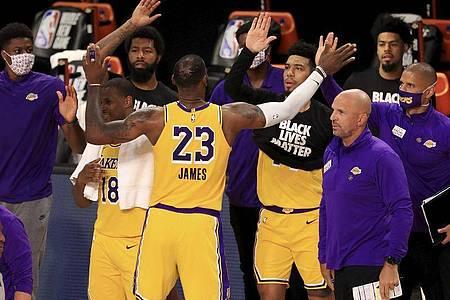 LeBron James (M) von den Los Angeles Lakers jubelt nach dem Spiel mit seinen Mannschaftskollegen. Foto: Mike Ehrmann/POOL Getty Images/AP/dpa