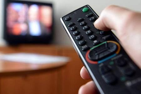Eine Hand hält eine Fernbedienung für ein Fernsehgerät. Foto: picture alliance / dpa