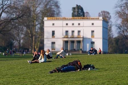 Menschen genießen das sonnige Wetter auf einer Wiese vor dem Jenisch-Haus in Hamburg. Foto: Jonas Walzberg/dpa