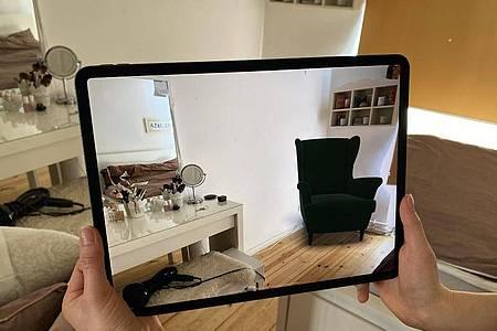 Ein Lidar-Sensor hilft, die reale Umgebung präzise zu erfassen. In dieser App von Ikea wird ein dunkelblauer Sessel virtuell in einem Zimmer platziert. Foto: Christoph Dernbach/dpa-tmn