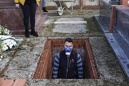 Ein Leichenbestatter in Spanien bereitet ein Grab vor während der Beerdigung einer 86-jährigen Frau mitten in der Corona-Krise. Foto: Bernat Armangue/AP/dpa