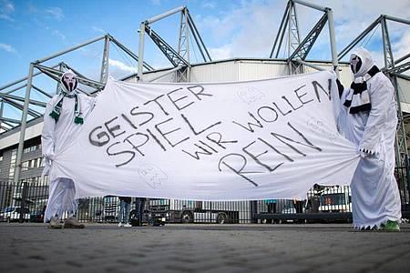 Vor verschlossenen Toren:Zwei als Geist verkleidete Gladbach-Fans vor dem Stadion. Foto: Jonas Güttler/dpa