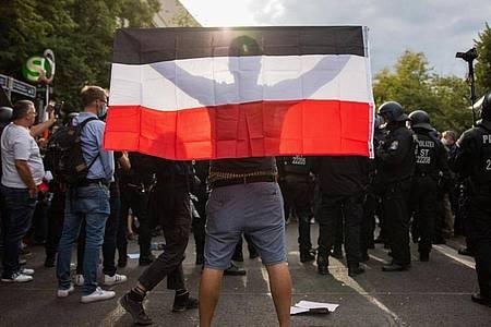 Ein Mann hält eine Reichsflagge bei einem Protest gegen die Corona-Maßnahmen vor der russischen Botschaft. Foto: Christoph Soeder/dpa