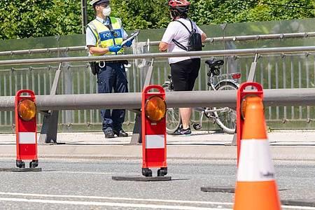 Ein deutscher Bundespolizist kontrolliert im Mai eine Fahrradfahrerin am bayerischen Grenzübergang Freilassing zwischen Deutschland und Österreich. Foto: Peter Kneffel/dpa