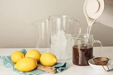 Fürs Grundrezept Eistee wird die doppelte Menge Schwarz- oder Grüntee mit heißem Wasser aufgegossen und ziehen gelassen. Foto: teeverband.de/dpa-tmn