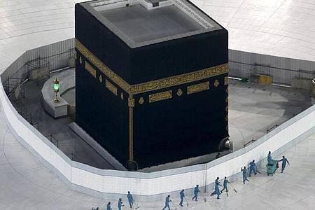 Arbeiter desinfizieren den Boden um die Kaaba, das quaderförmige Gebäude in der Großen Moschee. Foto: Amr Nabil/AP/dpa