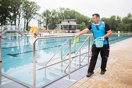 Neue Aufgaben: Der Schwimmmeister Björn Bendias in Ochtrup desinfiziert zwischen zwei Schwimmzeiten die Handläufe neben dem Schwimmbecken im Bergfreibad. Foto: Rolf Vennenbernd/dpa