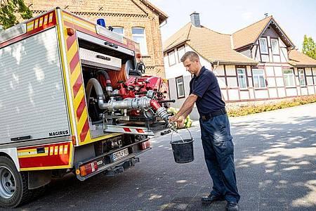 Einsatzkräfte der Freiwilligen Feuerwehr zapfen Löschwasser aus dem Tank eines ihrer Einsatzfahrzeuge. Foto: Moritz Frankenberg/dpa
