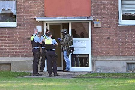Polizei und ein SEK-Beamter stehen vor der Eingangstür eines Mehrfamilienhauses inkrefeld. In einer Wohnung im Haus hat sich möglicherweise ein Mann mit vier Kindern verschanzt. Foto: Alexander Forstreuter/-/dpa