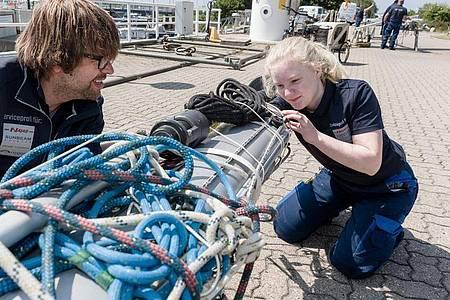 Motoren und Technik sind ihr Ding: Carina Isenberg prüft mit einem Kollegen Elektroleitungen in dem demontierten Mast einer Segeljacht. Foto: Markus Scholz/dpa-tmn