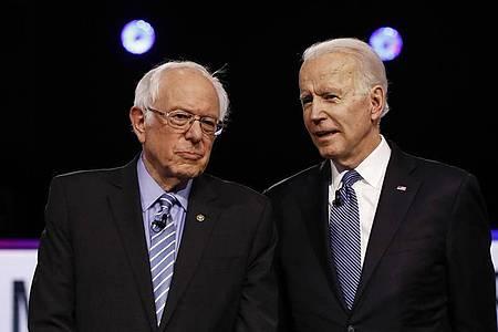 Bernie Sanders (l) und Joe Biden stehen im Februar während einer TV-Debatte nebeneinander. Foto: Matt Rourke/AP/dpa