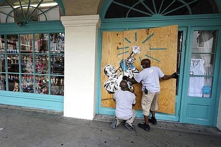 Arbeiter vernageln in Vorbereitung auf Sturm «Marco» die Scheiben eines Geschäfts in New Orleans. Foto: Gerald Herbert/AP/dpa