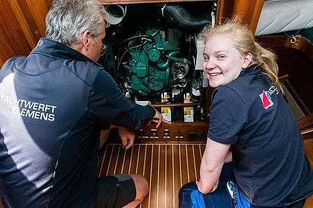 Ihr Arbeitsplatz ist die «Yachtwerft Klemens»: Werftbesitzer Thomas Schwarz zeigt Carina Isenberg einen Dieselmotor. Foto: Markus Scholz/dpa-tmn