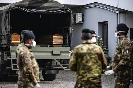 Italienische Soldaten mit Mundschutz vor einem Militärfahrzeug mit Särgen vonCorona-Opfern. Foto: Claudio Furlan/LaPresse/AP/dpa