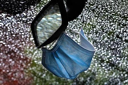 Ein medizinischer Mundschutz hängt am Rückspiegel eines Autos. Foto: Karl-Josef Hildenbrand/dpa