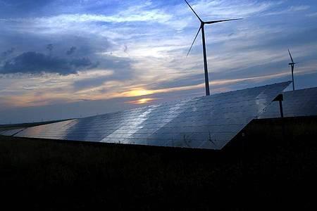 Der mit Wolken überzogene Abendhimmel spiegelt sich auf Solarzellen einer vor Windrädern stehenden Solarkraftanlage. Foto: Karl-Josef Hildenbrand/dpa