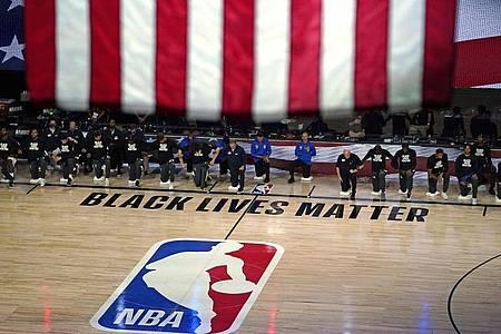 Die Spieler der Milwaukee Bucks und von den Orlando Magic knien vor dem Spiel nieder. Foto: Ashley Landis/AP/dpa