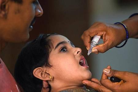 Ein Mädchen erhält während der zweiten Phase einer Impfkampagne Tropfen gegen Kinderlähmung. Foto: R Gnanasasthaa/PTI/dpa