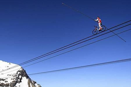 Der Schweizer Drahtseilkünstler Freddy Nock mit einem Fahrrad auf einem Seil einer Seilbahn. Foto: Laurent Gillieron/KEYSTONE/dpa
